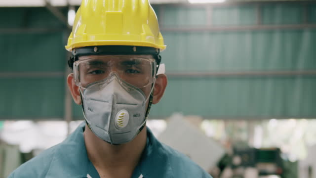 confident young industrial worker portrait, wearing mask, close up. slowmotion, asian male, overalls, helmets. industrial and manufactory concept. - tajowie filmów i materiałów b-roll