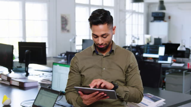 Confident young start up entrepreneur Male executive using a digital tablet in office and looking at camera. Happy young businessman working at start up. indian subcontinent ethnicity stock videos & royalty-free footage