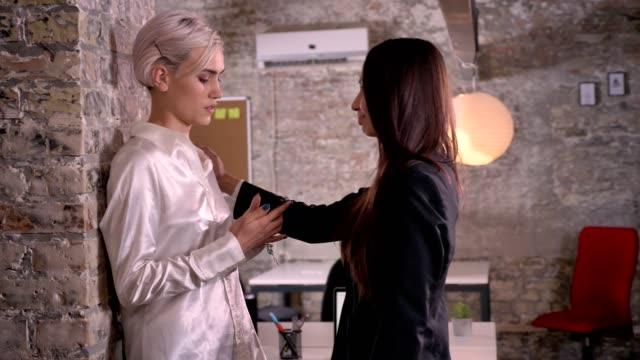 stockvideo's en b-roll-footage met zeker jonge vrouw duwen andere vrouw tot wand, vrouw gaat weg in moderne kantoor, lesbische concept - verleiding
