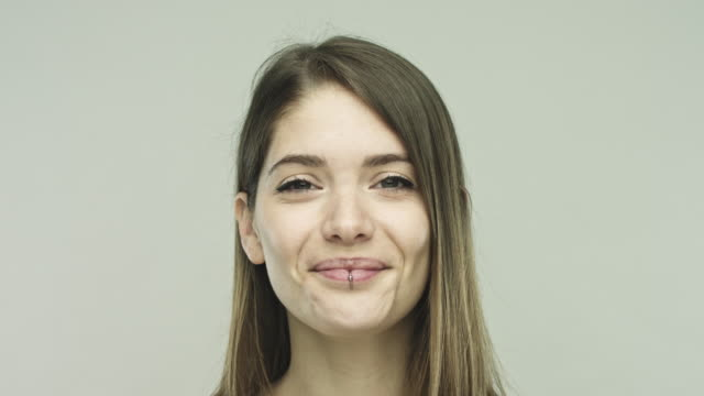 Confident young woman smiling on gray background Close up of confident young woman smiling against gray background. Footage of real woman looking at camera. Studio shot with sharp focus on eyes. front view stock videos & royalty-free footage