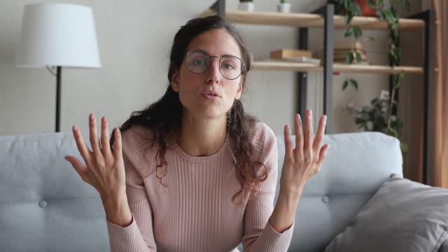 vidéos et rushes de jeune femme confiant parlant à l'appareil-photo à la maison - professeur(e)