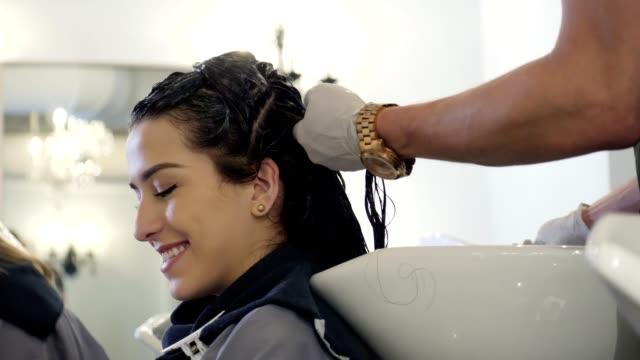 自信を持って若い女性は、ヘアサロンでスマート フォンを使用してください。 - 美容室のビデオ点の映像素材/bロール