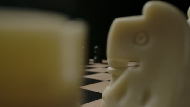 confrontation between black and white chess pieces. the beginning of the game - заколоченный стоковые видео и кадры b-roll