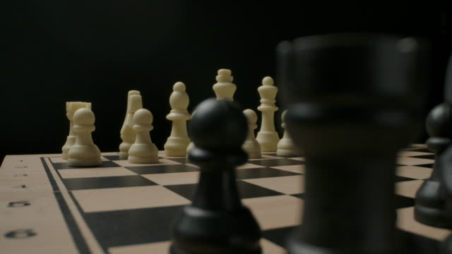 Confrontation between black and white chess pieces. The beginning of the game