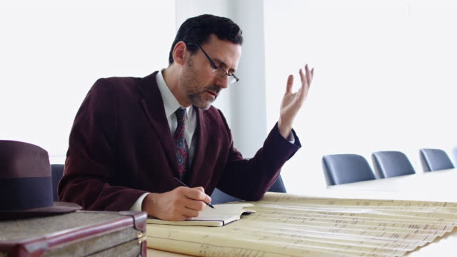 confused man taking notes from old plans - quarantenne video stock e b–roll