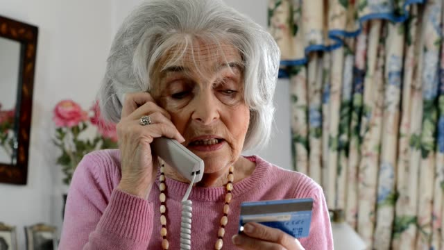 confused senior woman giving out credit card details over the phone - fraud stock videos & royalty-free footage