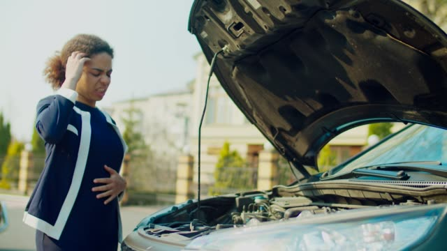 Confused woman looking at broken car engine on street