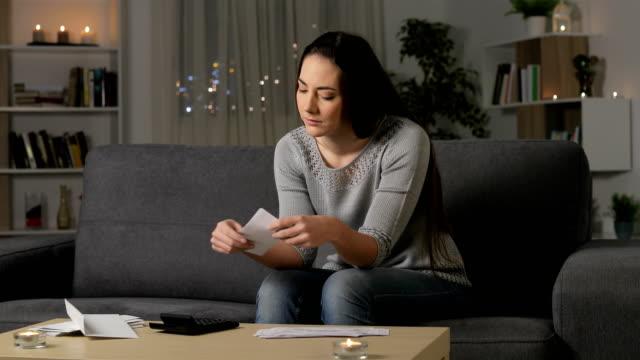 vidéos et rushes de femme confuse lisant des reçus de banque dans la nuit - bec