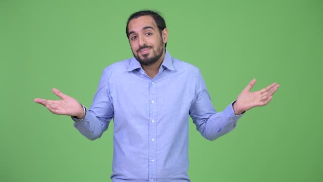 confused young bearded indian businessman shrugging shoulders - question mark video stock e b–roll