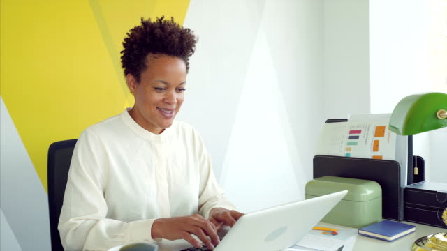 Connect your business. Businesswoman in her office working at laptop. She is confident and getting ready to deliver the best business results. happy boss stock videos & royalty-free footage