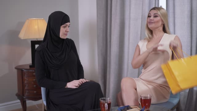 conservative muslim woman getting present from caucasian modern friend. young lady in hijab taking out candid dress with sparkles. cultural difference, diversity, discrepancy. - abbigliamento religioso video stock e b–roll