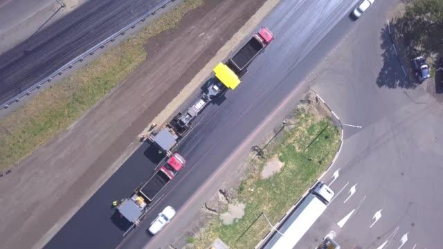 vídeos de stock e filmes b-roll de construction and repair of roads. asphalt laying. view from above - alfalto