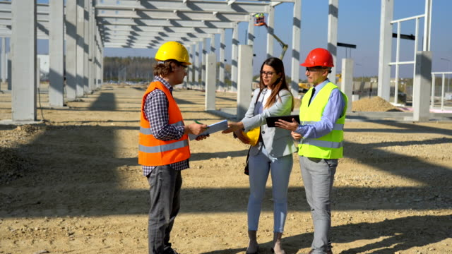 Construction Business Team Standing and Talking on Site Under Construction