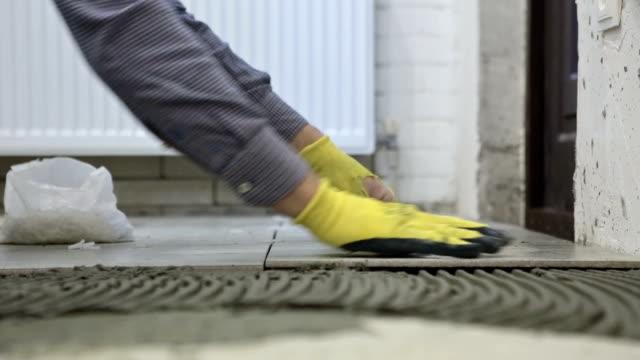 konstruktion. anläggning av fjärrnät med keramikplattor. - construction workwear floor bildbanksvideor och videomaterial från bakom kulisserna