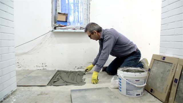 konstruktion. anläggning av fjärrnät med keramikplattor. - endast en medelålders man bildbanksvideor och videomaterial från bakom kulisserna