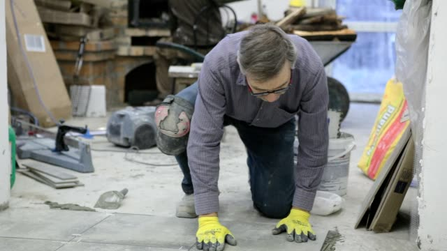 Construction. Construction work with ceramic floor tiles. video