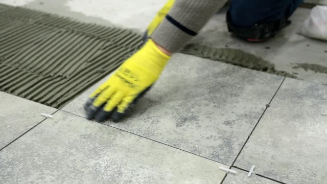 construction. construction work with ceramic floor tiles. - piastrella video stock e b–roll