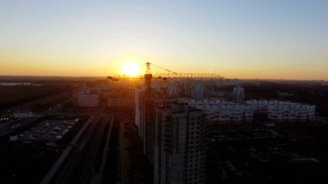 Construction crane at sunset. Aerial footage video