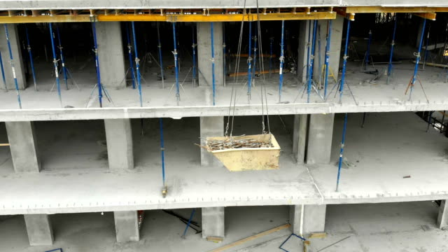 Construction crane lifts rebar on the construction site. Heavy load lifting by crane