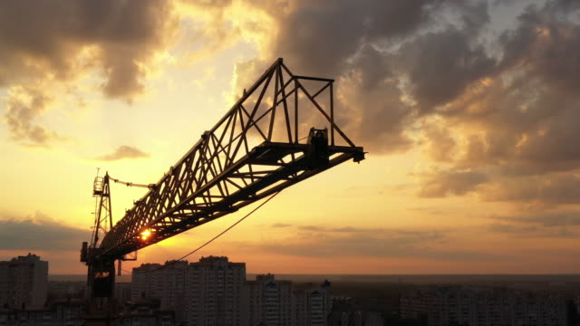 A construction crane swaying slightly in the wind against the morning sky. Close-up, aerial video