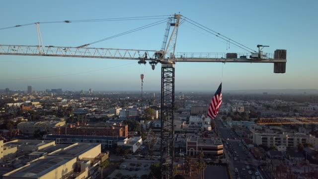 vídeos y material grabado en eventos de stock de grúa de construcción con bandera americana aérea drone tiro - grúa