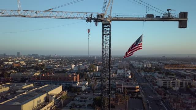 vídeos y material grabado en eventos de stock de grúa de construcción con bandera americana aérea drone tiro - american flag