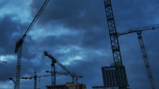 Construction cranes on a dark, cloudy sky. Construction site after sunset Crane silhouette on a construction site. Building industry development. foundation make up stock videos & royalty-free footage