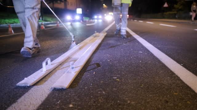 Bouw bemanning spray schilderij crosswalk strepen 's nachts video