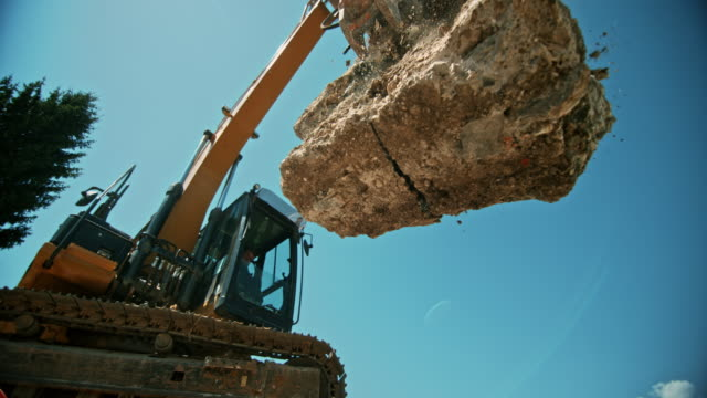 slo mo construction debris being released from the excavator and falling on a pile in sunshine - pietra roccia video stock e b–roll