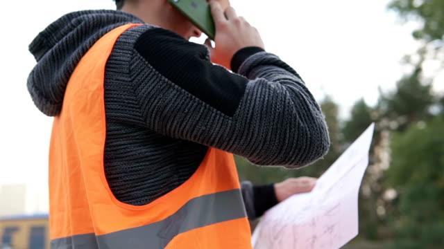 vídeos de stock e filmes b-roll de construction engineer conducts a telephone conversation with a customer at a construction site - obras em casa janelas