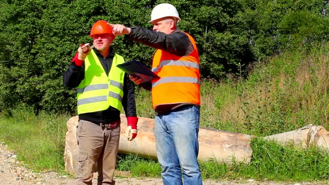 Construction Engineer explains to worker assigned work Construction Engineer explains to worker assigned work handbook stock videos & royalty-free footage