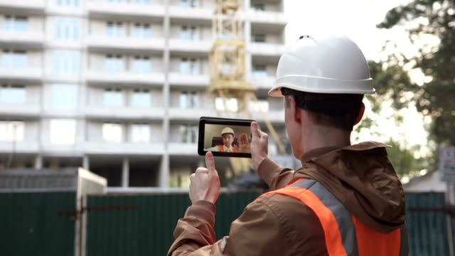 A construction engineer holds a video conference with the chief construction engineer, he talks about the work plan with a high-rise building, and uses a tablet computer. - vídeo