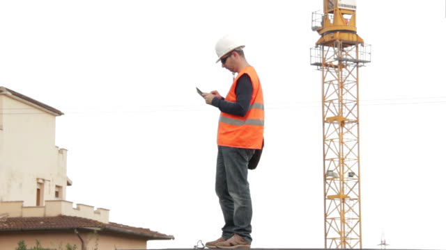 Construction engineer wearing safety vest with yellow crane on the background us video