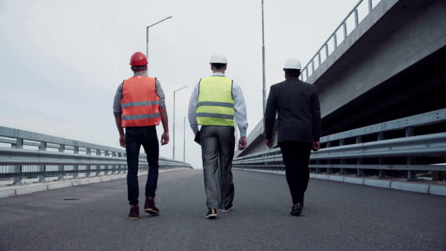 高速道路の傾斜路の上を歩いて建設エンジニア - 後ろ姿点の映像素材/bロール