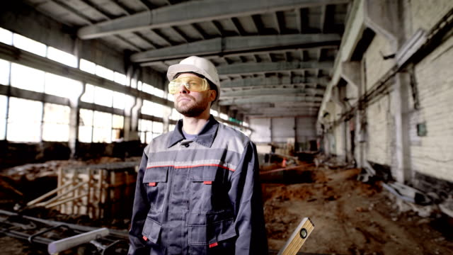 Construction. Foreman at the construction site. A man dressed in a special uniform at the construction site of an industrial facility Foreman at the construction site. A man with a helmet on his head and dressed in a special uniform on the construction site of an industrial facility. Helmet head protection at the construction site. handbook stock videos & royalty-free footage