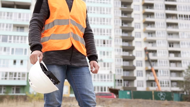 Construction foreman clothes a white helmet at a construction site - vídeo