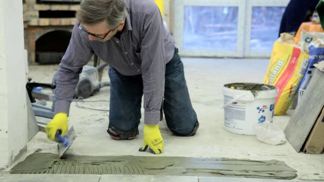 Construction in the mansion. Construction work with ceramic floor tiles. video