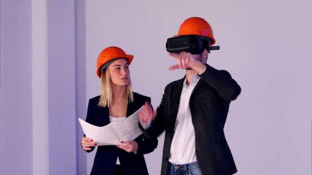 Bouw mannelijke en vrouwelijke ingenieurs in helmen met VR bril beheren bouwproject in 3d video