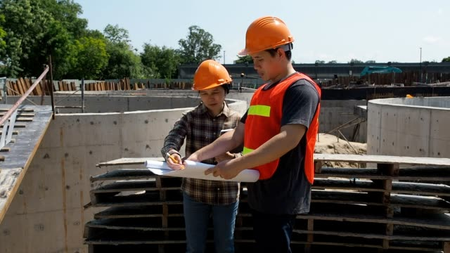 Construction manager and engineer discussing and checking plans on construction site. Construction manager and engineer discussing and checking plans on construction site. craftsman architecture stock videos & royalty-free footage