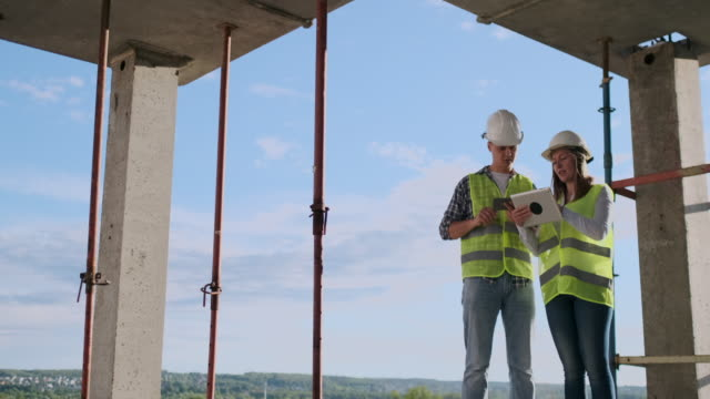 Construction manager and engineer working on building site. Construction manager and engineer working on building site general view stock videos & royalty-free footage