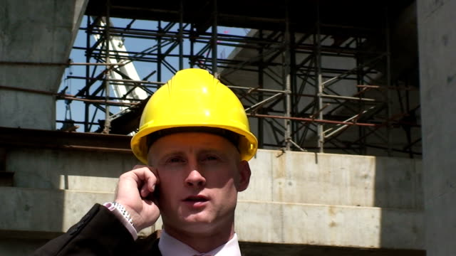 Construction manager on mobile A construction manager uses the mobile phone, on site. craftsman architecture stock videos & royalty-free footage