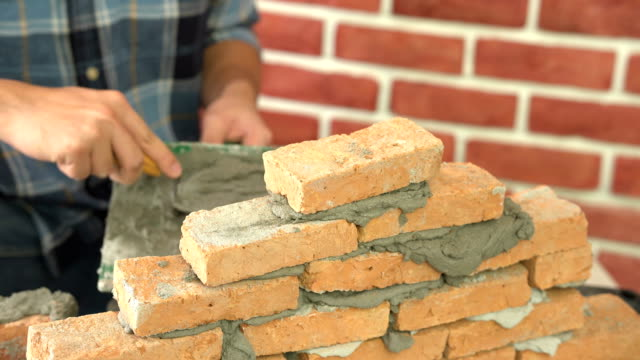 construction man's hand laying brick on Construction site with trowel