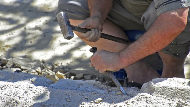 Construction manual worker with Sledge hammer hitting concrete block video