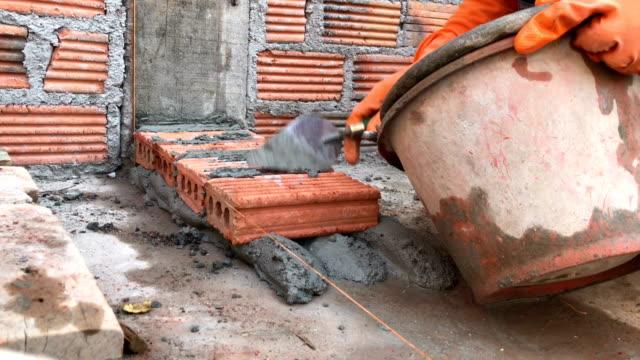 Construction mason worker bricklayer installing red brick. video