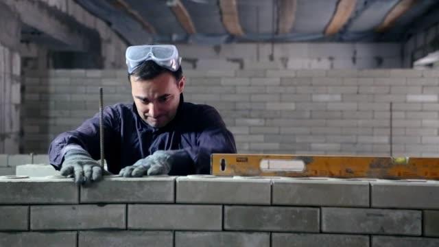 bir tuğla duvar inşaatı. - bir orta yetişkin erkek sadece stok videoları ve detay görüntü çekimi