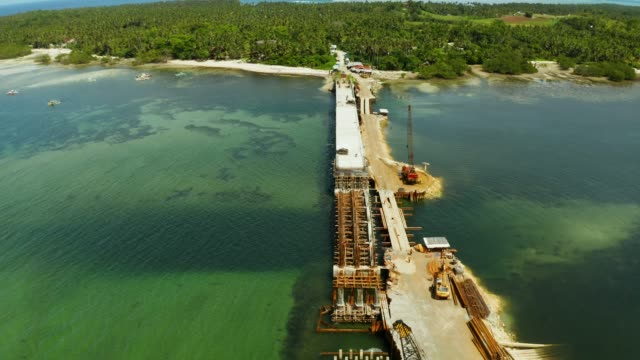 Construction of a bridge across the bay. Construction equipment on the bridge, top view. Siargao, Philippines