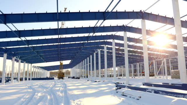 Construction of a modern factory or warehouse, modern industrial exterior, panoramic view, Modern storehouse construction site, the structural steel structure of a new commercial building