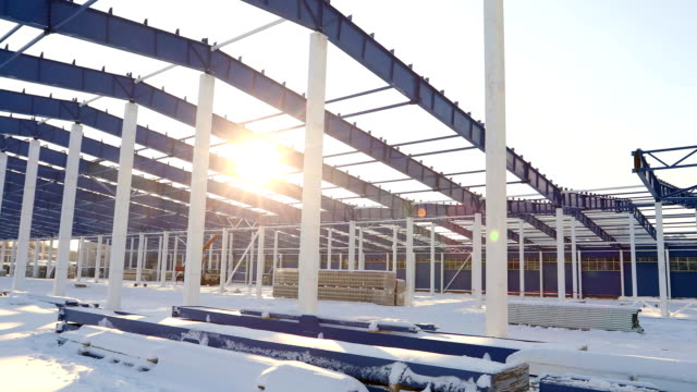 construction of a modern factory or warehouse, modern industrial exterior, panoramic view, modern storehouse construction site, the structural steel structure of a new commercial building - acciaio video stock e b–roll