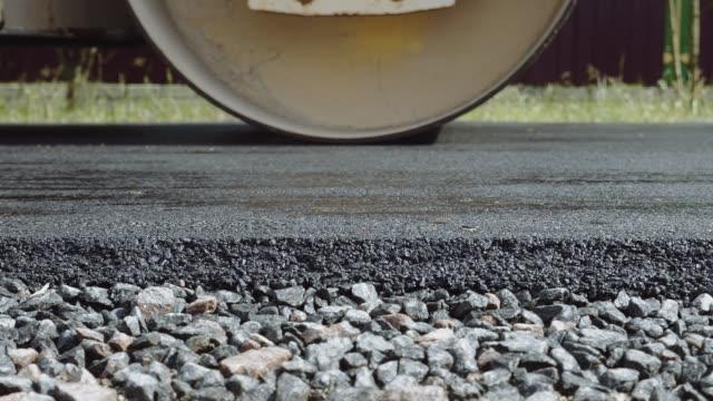 bau einer neuen straße. die walzenstufen und verdichtet den asphalt - asphalt stock-videos und b-roll-filmmaterial