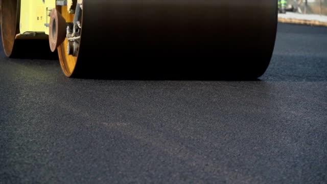 строительство асфальтовой дороги. укладка дорожного полотна ролика. уплотнение дорожного покрытия во время строительства. - бетон стоковые видео и кадры b-roll